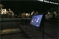 A monitor shows the conductor during a rehearsal of 'Die Soldaten' at the Park Avenue Armory.